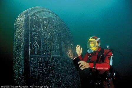 Дайвер Франк Годдио позирует с покрытой надписями плитой, которую он нашел в руинах Гераклеона в Абу-Кир, Египет