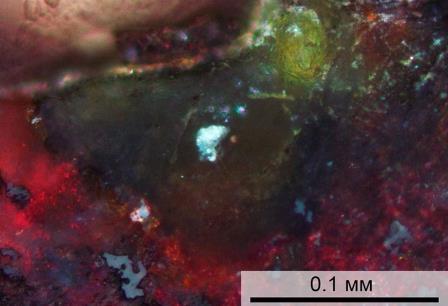 Микрофотография минерала, обнаруженного в бассейне Мертвого моря. Желто-зеленый агрегат — циклофосфат, красный — гематит (оксид железа). © Britvin et al / Geology, 2020
