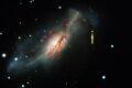 """Цветное композитное изображение от Обсерватории Лас-Кумбрес и космического телескопа """"Хаббл"""" сверхновой с электронным захватом в 2018zd (обозначена стрелкой) и ее галактика со взрывом звездообразования NGC 2146 (слева от нее) © NASA/STSCI/J. Depasquale; Las Cumbres Observatory"""